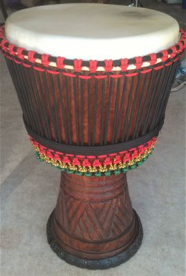 djembe drum made of acajou wood with cowskin head reheaded by drumsticktony. Beautiful red, yellow and green rope custom cradle loops